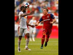 New York Red Bulls defender Kemar Lawrence (left) heads the ball in front of Real Salt Lake forward Corey Baird during the first half of an MLS soccer match Saturday, June 1, 2019, in Harrison, New Jersey.