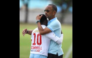 St George's College's player Nathanniel Campbell embraces his coach Neville Bell during a Manning Cup match at Winchester Park on September 9, 2019.