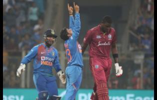 India's Kuldeep Yadav (center) celebrates the dismissal of Windies batsman Jason Holder (right) during their third Twenty20 International cricket match in Mumbai, India yesterday.