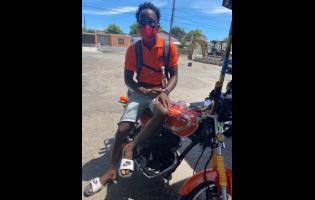 PNP supporter Junior Gayle shows off his orange motorbike.