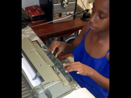 Eleven-year-old Destiny Morrison using the Braile machine.